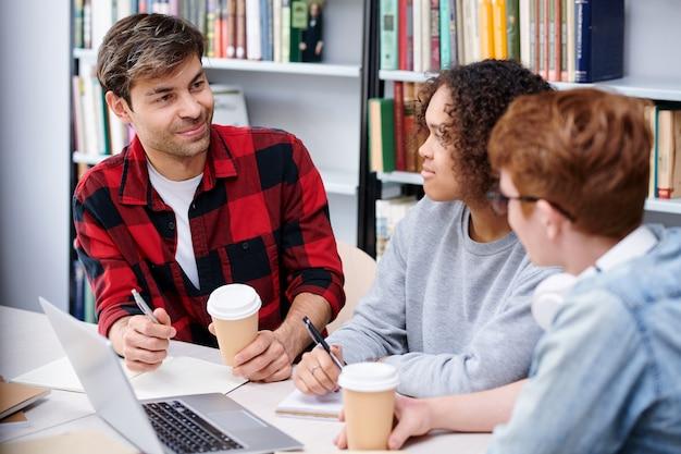 Alunos amigáveis com café, discutindo seus trabalhos escolares ou tarefas de casa enquanto estão sentados na biblioteca Foto Premium