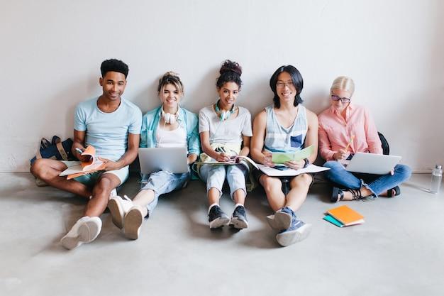 Alunos animados com laptops e livros didáticos se preparando para o teste sentados no chão. retrato interno de amigos internacionais estudando juntos antes dos exames. Foto gratuita