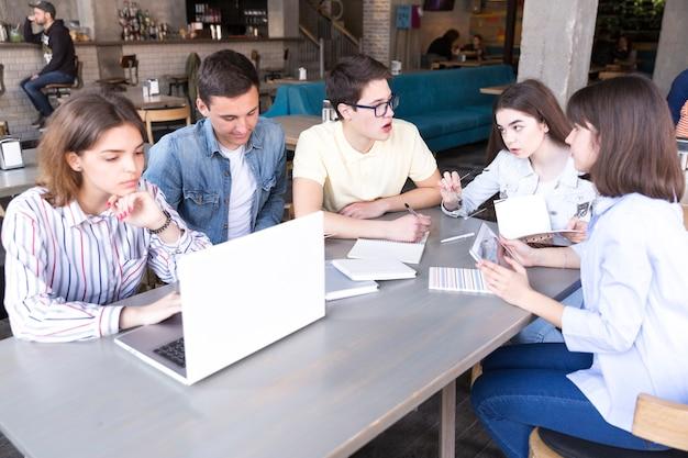 Alunos aprendendo juntos no café Foto gratuita