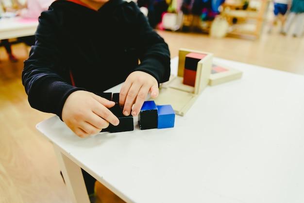 Alunos do ensino fundamental em uma escola usando materiais de madeira de educação alternativa. Foto Premium