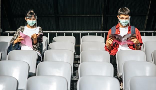 Alunos do sexo masculino e feminino usam máscaras, sentam e leem na cadeira de campo Foto gratuita