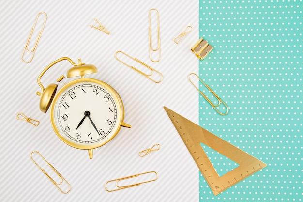 Alunos e material escolar dourado com despertador. volta à escola e escritório papelaria idéia Foto Premium