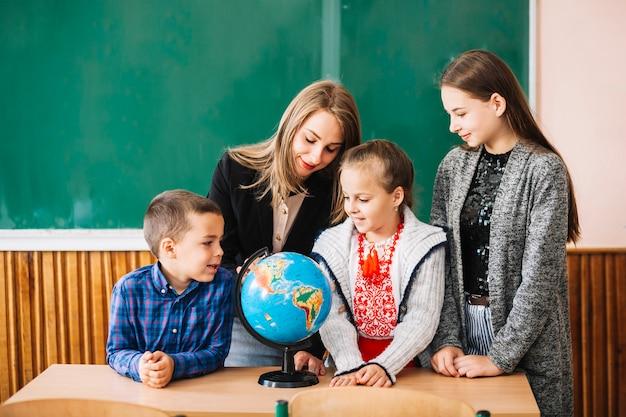 Alunos e professor da escola a olhar para o globo Foto Premium