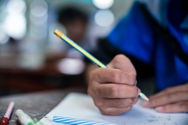 Alunos escrevendo e lendo exercícios de folhas de respostas para exames na sala de aula da escola com estresse Foto Premium