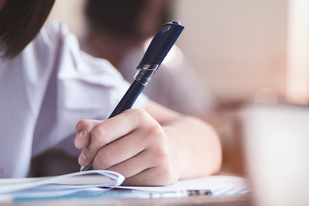 Alunos escrevendo resposta fazendo exame em sala de aula Foto Premium