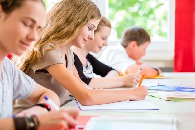 Alunos escrevendo um teste na escola de concentração Foto Premium