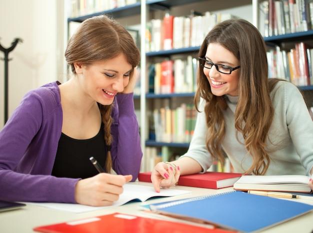 Alunos estudando juntos em uma biblioteca   Foto Premium