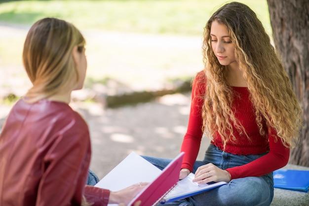 Alunos estudando juntos, sentado em um banco ao ar livre Foto Premium