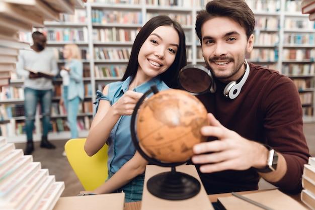 Alunos inteligentes estão usando o globo na biblioteca Foto Premium