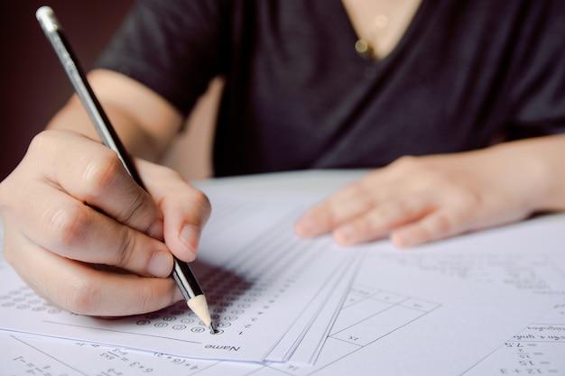 Alunos mão segurando o lápis escrevendo escolha selecionada em folhas de respostas e folhas de questão de matemática Foto Premium