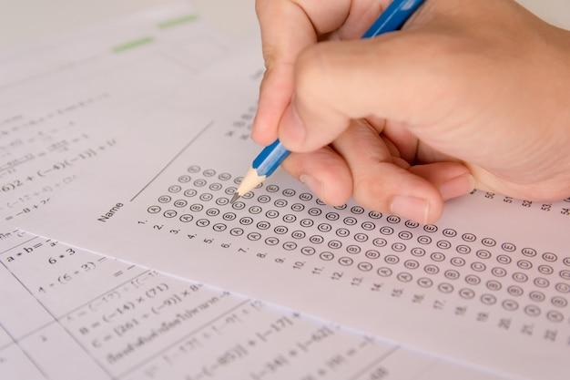 Alunos mão segurando o lápis escrevendo escolha selecionada em folhas de respostas e matemática ques Foto Premium