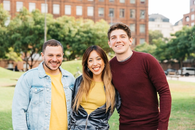 Alunos sorrindo para a câmera no campus da faculdade Foto gratuita