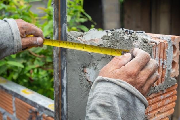 Alvenaria trabalhador da construção que constrói uma parede de tijolo. Foto gratuita