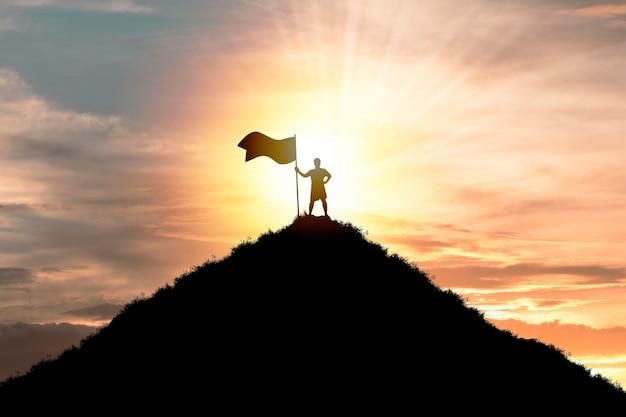 Alvo objetivo de realização de negócios e conceito de sucesso, homem silhueta em pé e segurando a bandeira no topo da montanha com céu de nuvem e luz solar. Foto Premium
