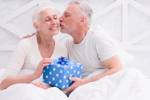 Amado marido beijando sua esposa na bochecha segurando a caixa de presente azul na mão Foto gratuita
