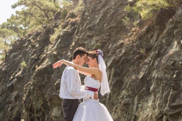 Amando o casal de noivos na praia, noiva e noivo Foto Premium