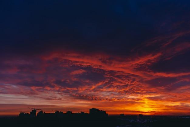 Amanhecer de vampiro vermelho sangue ardente. fogo dramático quente surpreendente azul céu nublado escuro. luz do sol laranja. fundo atmosférico do nascer do sol em tempo nublado. nebulosidade intensa. aviso de nuvens de tempestade. copyspace Foto Premium