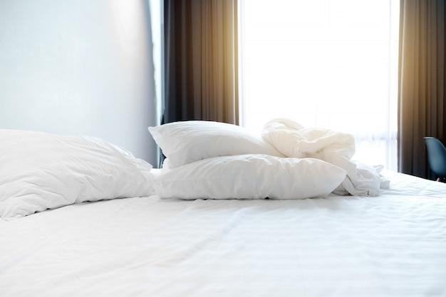 Amanhecer no quarto branco da cama com edredão e o descanso amarrotados na cama. Foto Premium