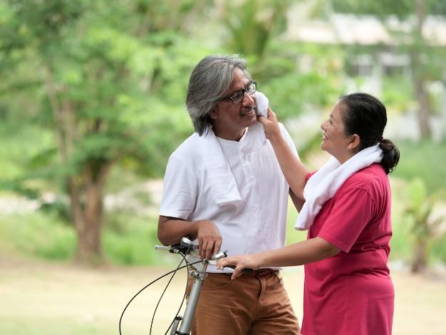 Amante casal sênior, andar de bicicleta no parque Foto Premium