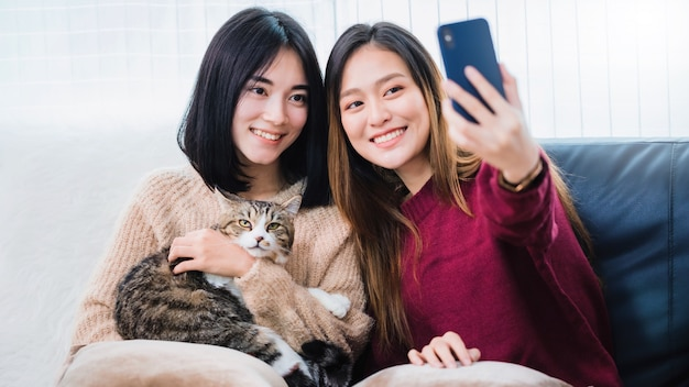 Amante de casal de lésbicas lindas mulheres asiáticas jovens usando o smartphone selfie gato bonito animal de estimação na sala de estar em casa com cara sorridente. conceito de sexualidade lgbt com estilo de vida feliz juntos. Foto Premium