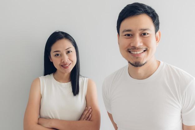 Amante feliz dos pares no t-shirt branco e no fundo cinzento. Foto Premium