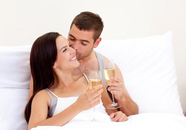 Amantes bebendo champanhe na cama Foto Premium