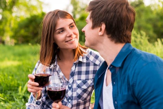 Amantes de sorriso novos que clinking vidros do vinho fora Foto gratuita