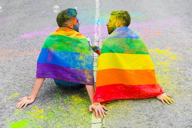 Amantes homens sentados na estrada de asfalto Foto gratuita
