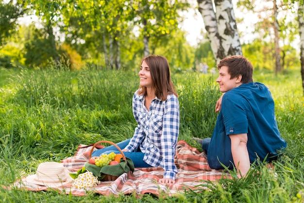 Amantes novos que sentam-se no cobertor na floresta do vidoeiro Foto gratuita