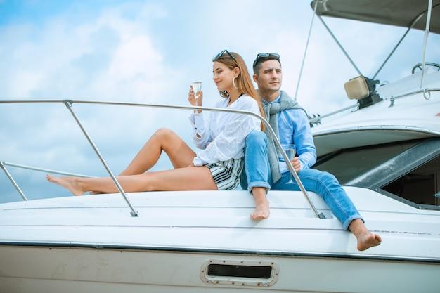 Amantes que passam o tempo feliz em um iate no mar. honeymood de luxo em um barco marítimo. conceito de férias, viagens, mar, amizade e pessoas. casal sorridente, sentado e conversando no convés do iate Foto Premium