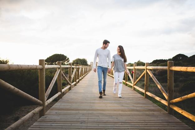 Amar casal andando em uma ponte pela mão Foto gratuita