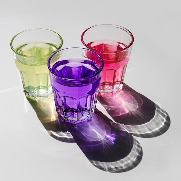 Amarelo; bebida-de-rosa e roxa em copos com sombra no fundo branco Foto gratuita