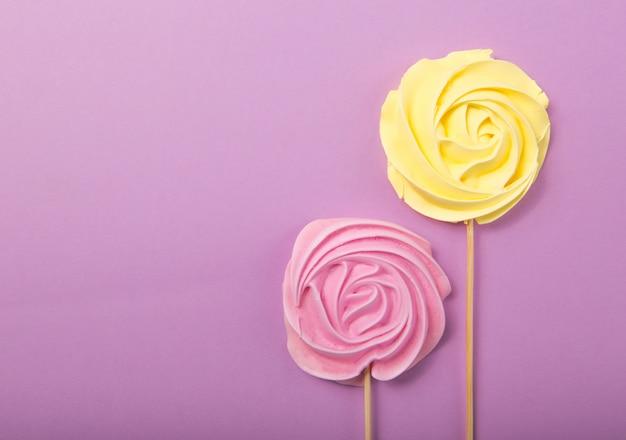 Amarelo e rosa doce de rosa em tons pastel, em uma vara de madeira sobre um fundo cinza, dia dos namorados, dia das mães. Foto Premium