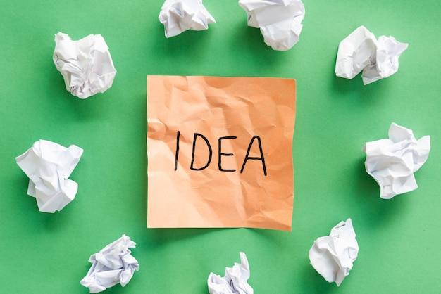Amassar papel ao redor por nota adesiva laranja com texto de idéia sobre fundo verde Foto gratuita