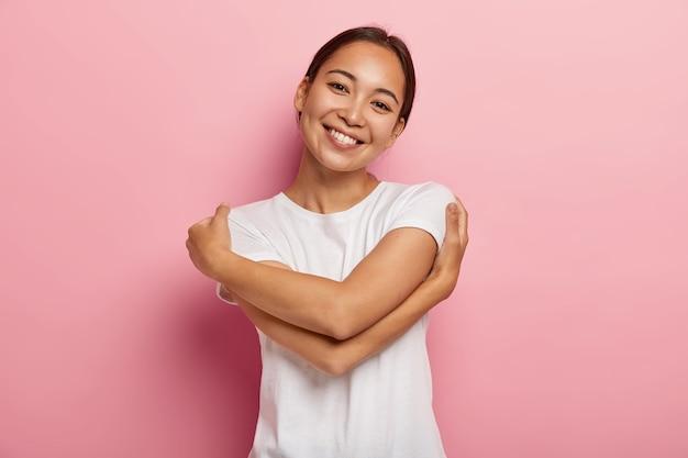 Ame a si mesmo. muito feliz menina asiática se abraçar, sentir conforto e cuidado, inclinar a cabeça, usar camiseta branca, não tem maquiagem, isolada sobre uma parede rosada, pensa no amante, quer estar em seus braços quentes Foto gratuita