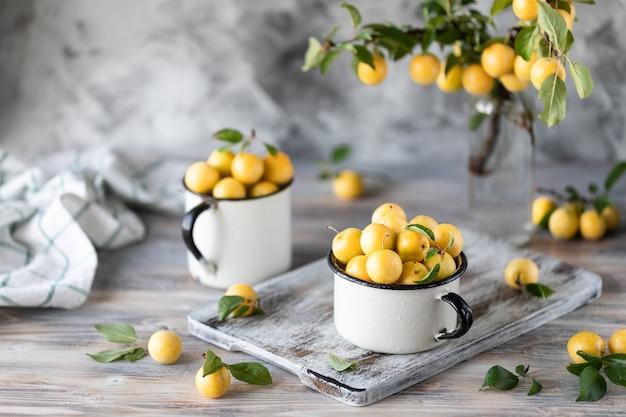 Ameixa amarela nas canecas brancas do ferro na tabela branca. colheita de ameixa de cereja com folhas verdes Foto Premium
