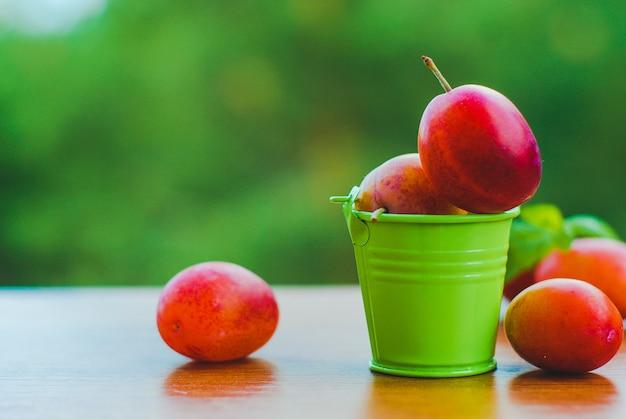 Ameixas orgânicas frescas no pequeno balde Foto Premium