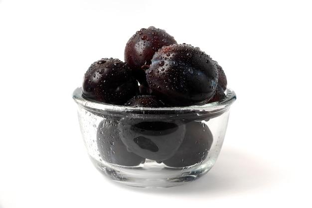 Ameixas pretas em copo de vidro Foto gratuita