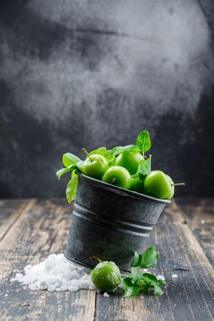 Ameixas verdes em um mini balde com cristais de sal, deixa a vista lateral na parede de madeira e enevoada Foto gratuita