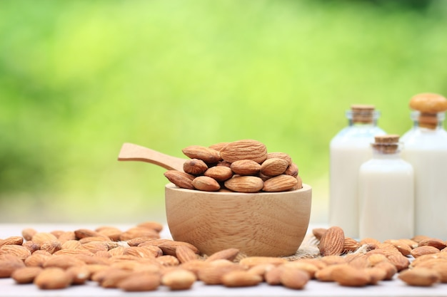 Amêndoa em uma tigela e leite de amêndoa em garrafa de vidro sobre a mesa turva fundo verde natural Foto Premium