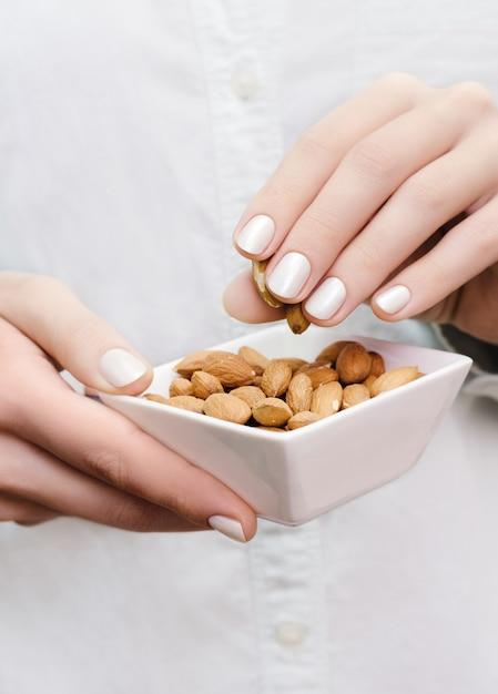 Amêndoas em tigela branca nas mãos de mulher Foto Premium