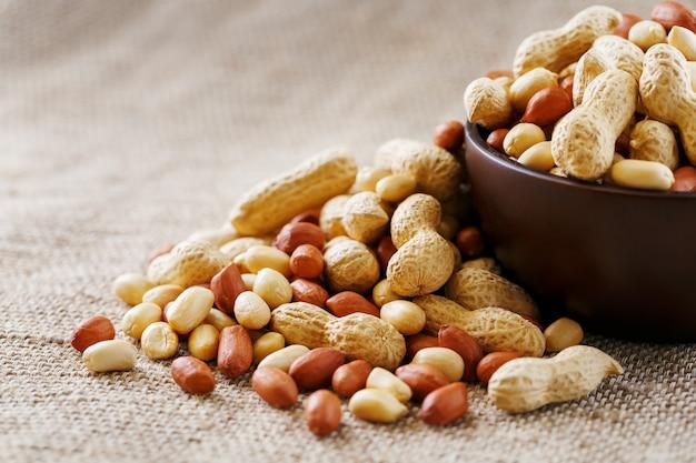 Amendoim com casca e descascado close-up em copos. amendoins torrados em casca e descascados em um pano marrom. Foto Premium