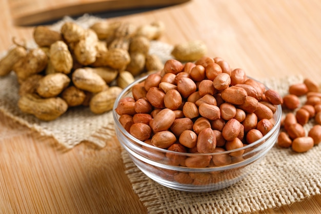 Amendoins em tigela sobre o fundo de madeira. Foto Premium