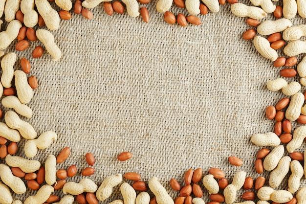 Amendoins roasted em um escudo e descascados em um fundo marrom da tela. Foto Premium