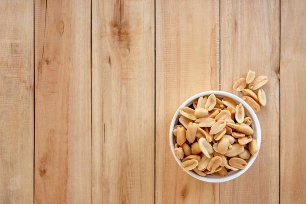 Amendoins salgados assados em uma tigela de cerâmica no fundo de madeira Foto Premium