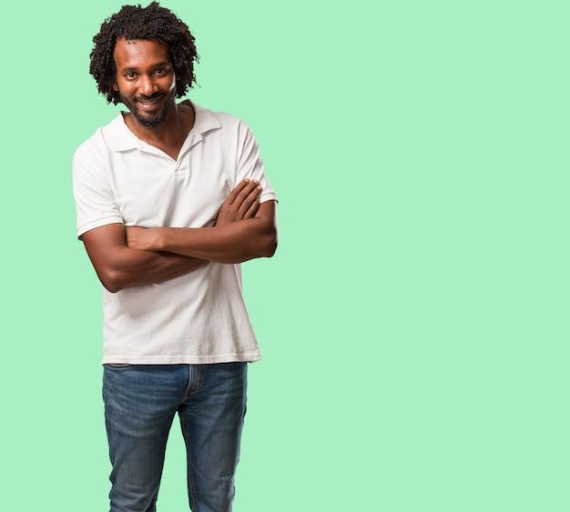 Americano africano considerável que cruza seus braços, sorrindo e felizes Foto Premium