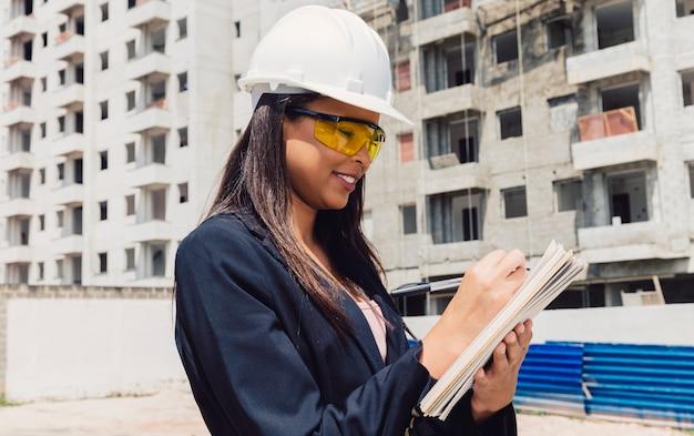 Americano africano, senhora, em, capacete segurança, com, notepad, perto, predios, construção Foto gratuita