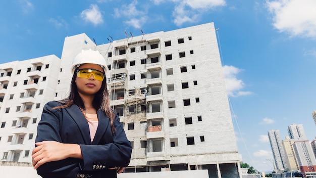 Americano africano, senhora, em, capacete segurança, e, óculos, perto, predios, construção Foto gratuita