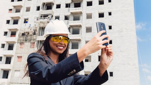 Americano africano, senhora, em, capacete segurança, levando, selfie, perto, predios, construção Foto gratuita
