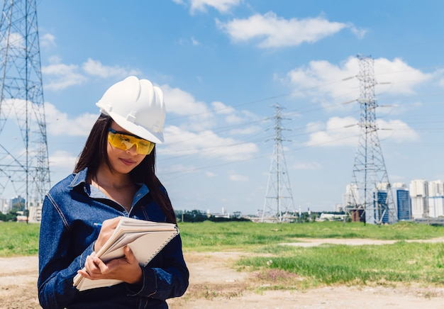 Americano africano, senhora, em, capacete segurança, notas levando, perto, linha alta voltagem Foto gratuita